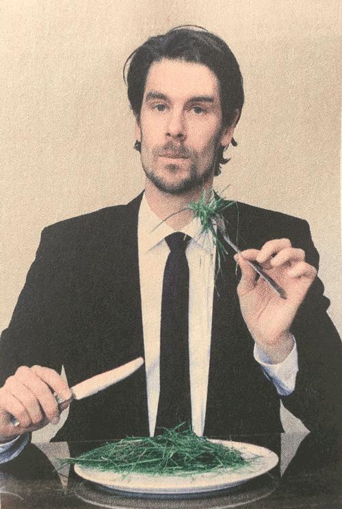 Mann mit Messer und Gabel der Gras isst